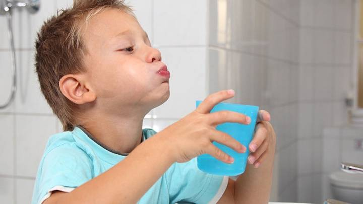 Мальчик полоскает рот для снятия опухоли