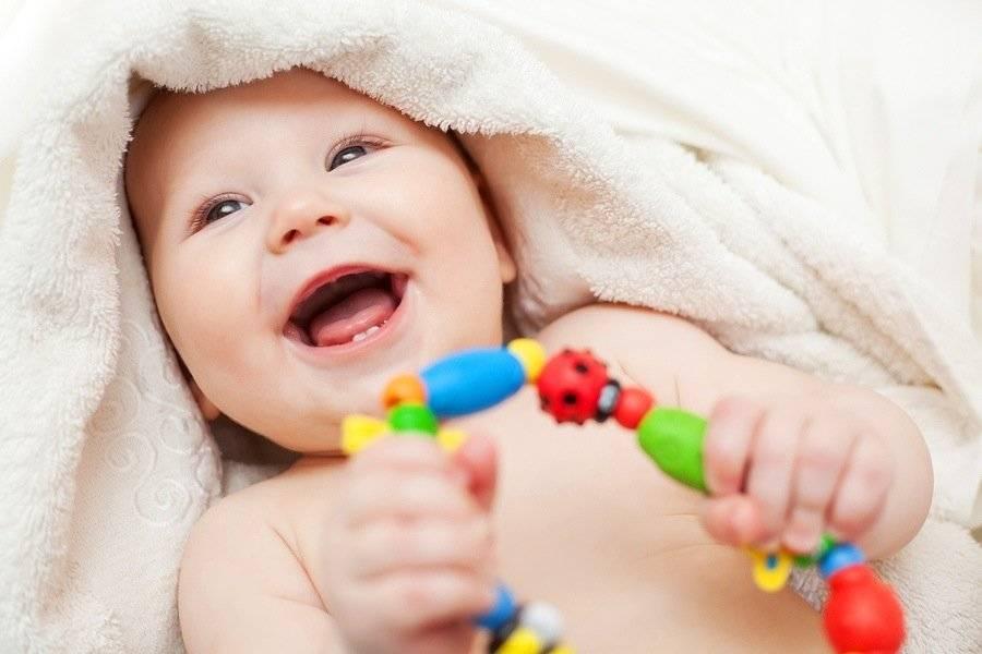 ребенок держит игрушку в руках и смеется