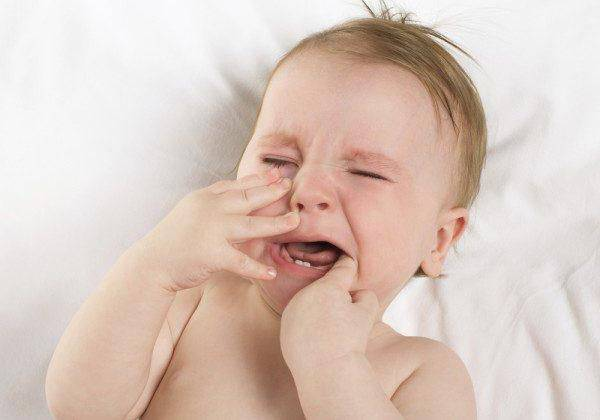 Мальчик плачет и сует палец в рот