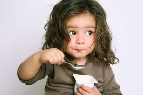Девочка ест ложкой йогурт