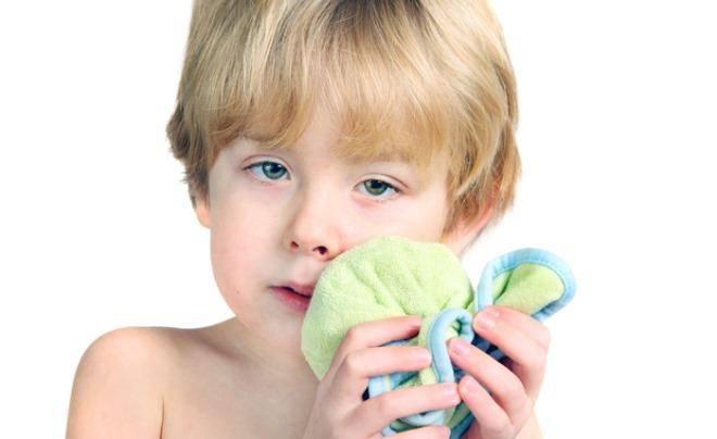 ребенок держит полотенце возле щеки